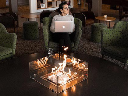 a woman with her macbook and a fireplace